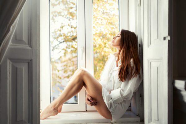 beautiful-young-woman-sitting-by-window-alone-Z6PWVD3-1024x683